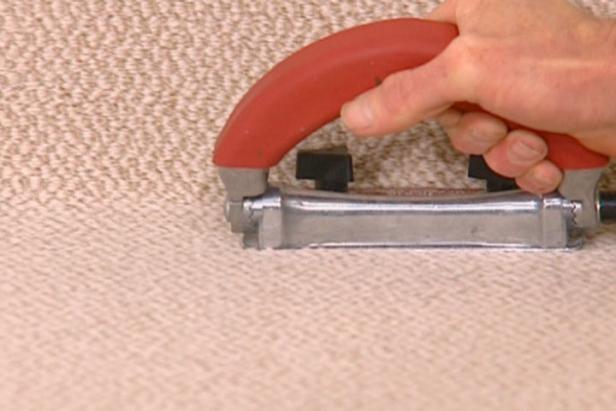 trimmer trims excess carpet against baseboard