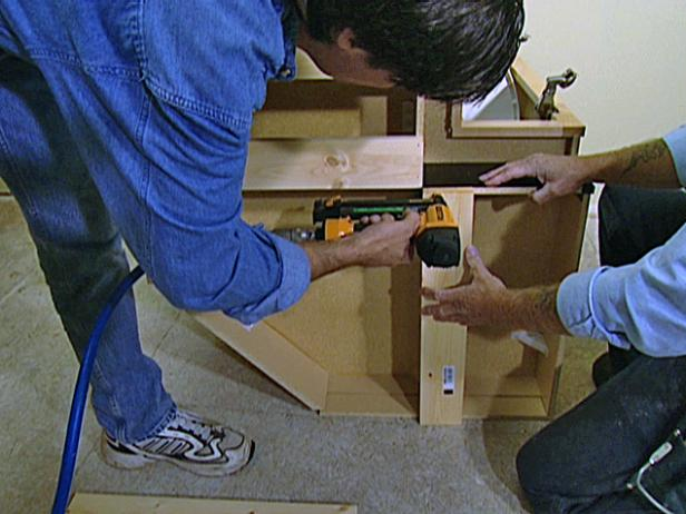 Turn each of the cabinets on its side and attach a pine 1x4 board to the bottom of the framework.