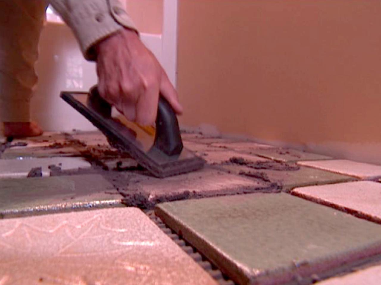 spread grout across floor with a float. How to Tile a Master Bath Floor   how tos   DIY