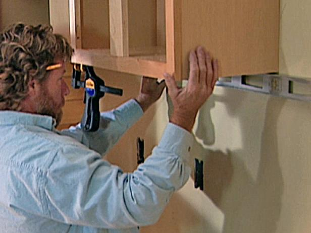 Once the second cabinet is adjusted so that it is perfectly level, the installers attach it to the wall using specialized wood screws.