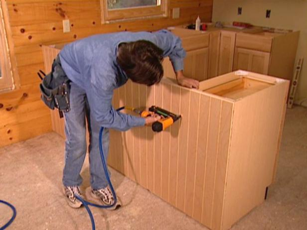 With the plywood reinforcement installed, attach the prefinished wainscoting to the visible back of the cabinets.