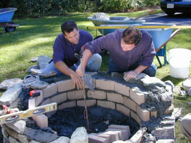Continue building the wall of the fire pit by alternating layers of face stone and fire brick until desired height is reached. Apply a bed of mortar on top of the previous layer of stone or fire brick and then set stones and bricks. Avoid wall weakness by staggering the joints between previous and subsequent layers of stone and brick. Fill in any gaps between the fire brick and the stone with mortar and stone scraps.