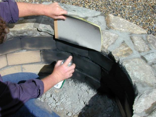 Spray paint the fire brick on the inside of fire pit with black stove paint so the focus of the fire pit is on the outside stone work not the sooty inside. When spraying, hold a piece of cardboard against the rim of the pit to protect the stone.