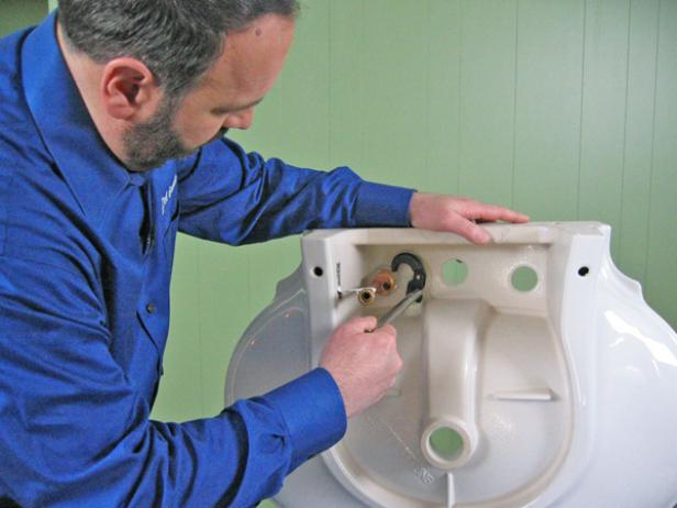 "Use a roll of plumber's putty around the seal to make sure it's water tight. Insert the valve bodies into the proper mounting holes, ensuring that the valve body marked ""cold"" is installed to the right of the center hole. Once the valve body is in place, slide the metal washer and nut onto the base, and then tighten it down."