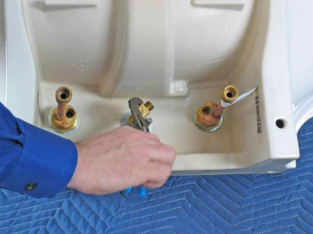 With the hardware mounted on the topside of the sink, mount the supply lines underneath. Screw the supply tee to the bottom of the spout, and then tighten it up with a pair of slip joint pliers.