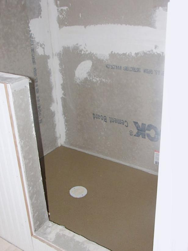 Have a professional install a shower membrane and shower pan appropriate for the space. Here, the shower pan is poured concrete (Image 2).