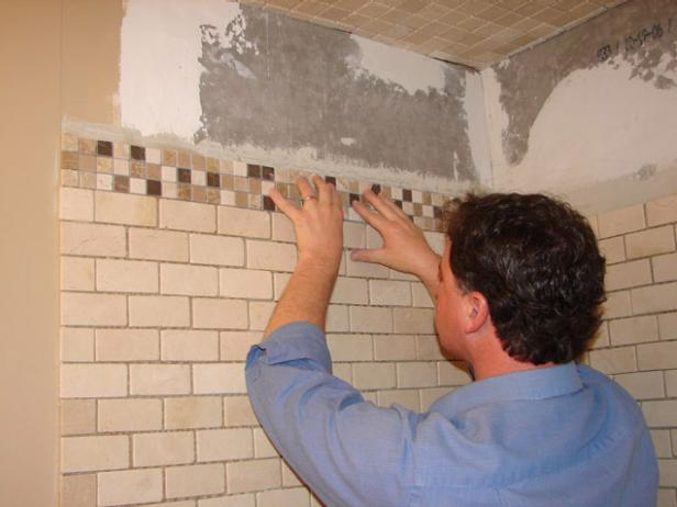 Add a decorative mosaic border to the top of the shower walls for visual interest.