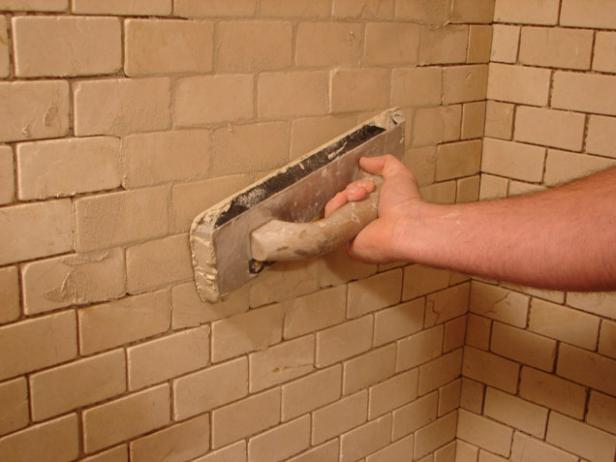 Use a rubber float to apply the grout. Start at the bottom and work up, keeping the float at an angle to the joints.