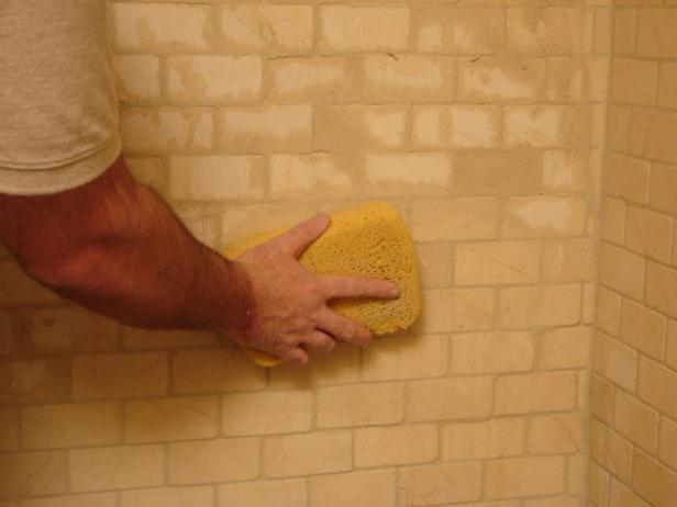Once all the joints in a section are filled, let it dry a little bit, then wipe the grout off the surface with a sponge and clean water.