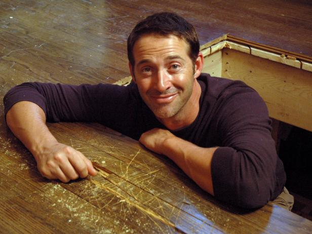 Josh Temple, host of Disaster House, crawls out of the hole in the hardwood floor to smile at the camera.