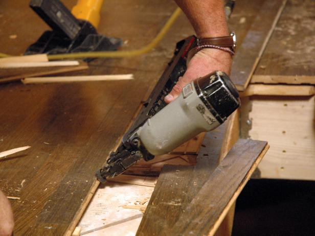 Close up of contractor using a nail gun on a damaged hardwood floor in the disaster house for repair.