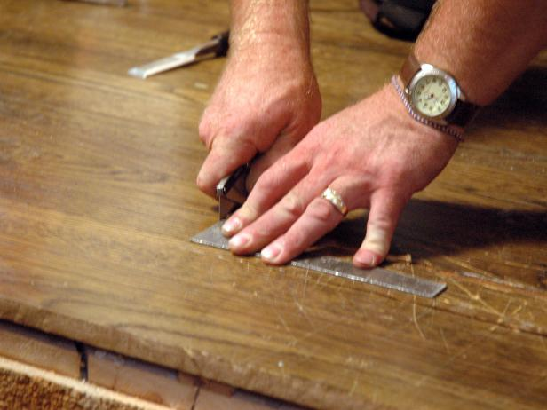 Contractor makes a straight cut on the hardwood floor to repair damage in the Disaster House.