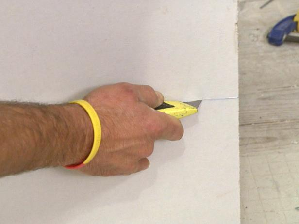 Close up of an exactor knife being used to cut into drywall in this home repair project.
