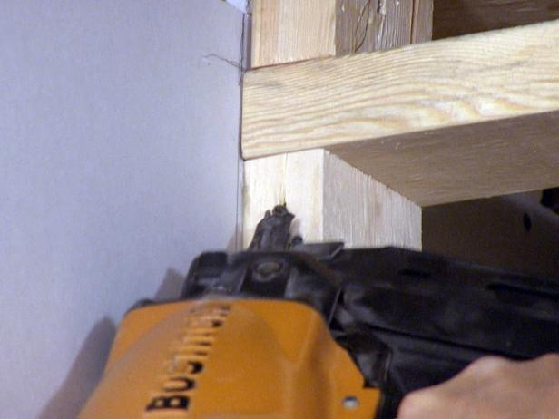 Close up of contractor using a tool to install box frame in this home repair project.