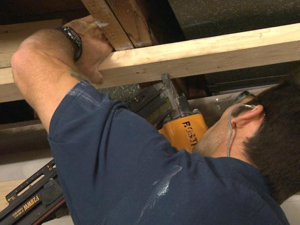 Man using a tool to install ceiling plates in this home repair project.