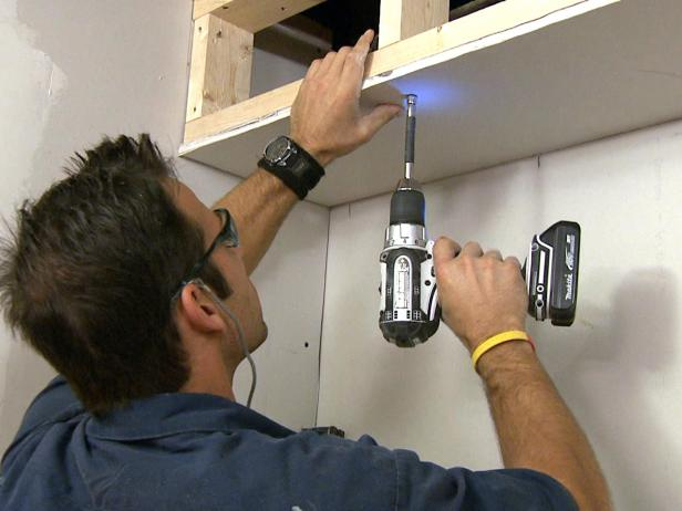 Man using a drill to install drywall on this home improvement project.