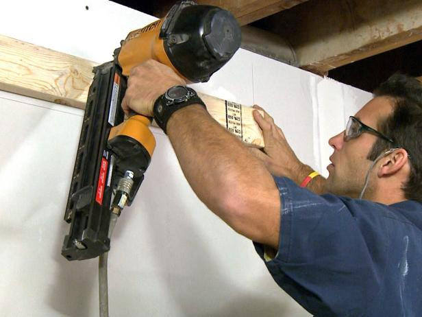 Contractor usings a tool to install wood wall plates in this home improvement project.