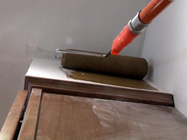 Using a roller brush to paint wall with brown paint.