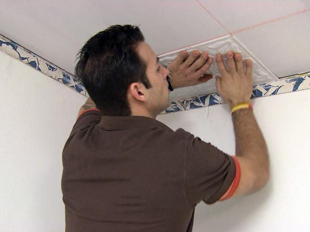 Marc installs tin ceiling tiles in the room of this home improvement project.