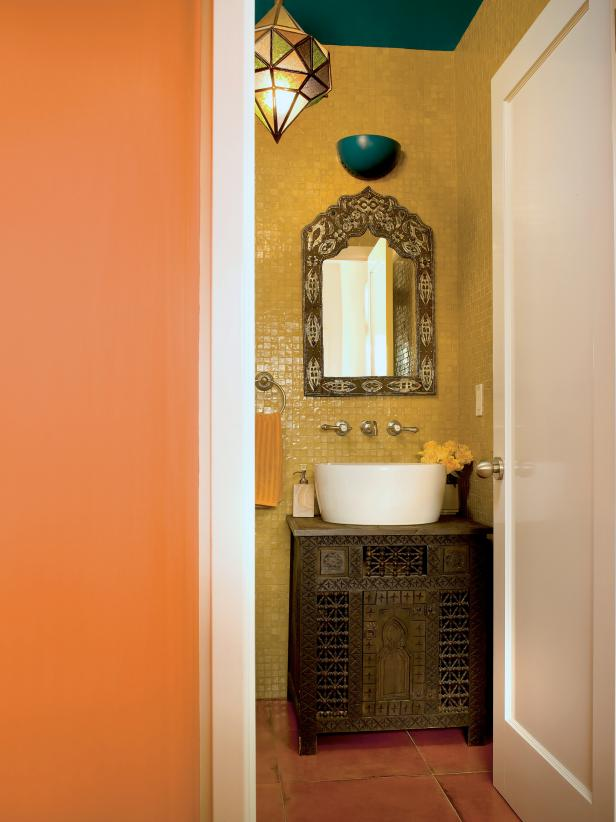 Sand Colored Powder Room With White Vessel Sink Atop a Carved Wood Moroccan Vanity