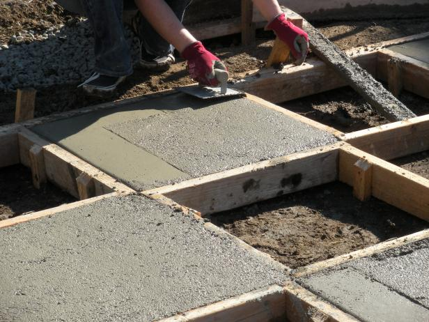 Pour concrete into the squares that don't have stakes in the middle of them. The concrete will go in the open areas between the square frames so they measure exactly 2' x 2'. Once the squares are poured, trowel the top until it's smooth. Add a powder color hardener over the top if you would like a pop of color and trowel it in until it's incorporated.