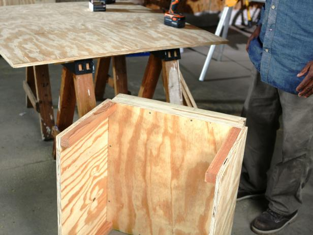 Constructing doghouse, side panels attached together.