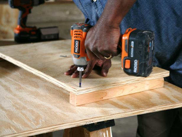Constructing a dog house, while attaching the wood pieces together using a drill.