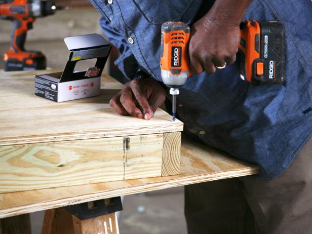 Closeup of man using a drill to attach plywood to base frame of doghouse construction project.