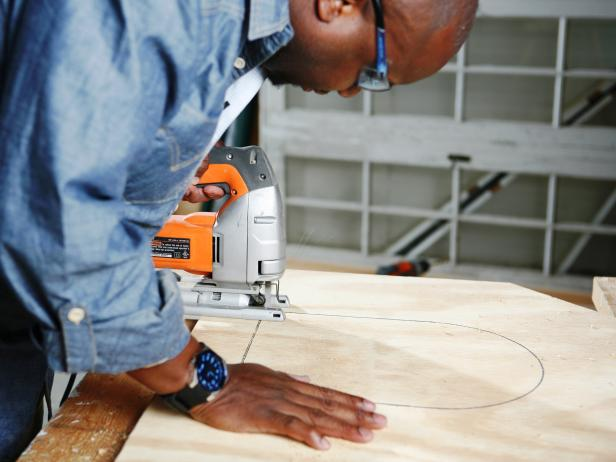 Man uses a saw to cut out traced area on plywood.