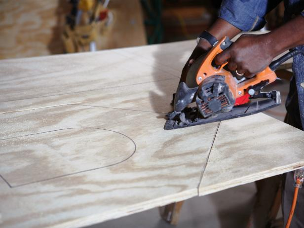 A circular saw is used to cut panels for a DIY doghouse.