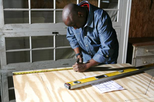African american man draws next to a measuring top on a piece of wood to construct a doghouse.