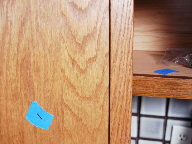Blue painters tape used to number the cabinet doors.