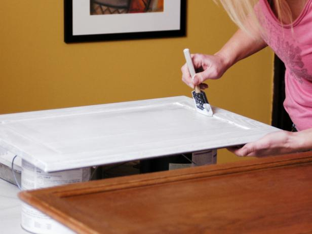 Woman paints cabinet with sponge brush using white paint.