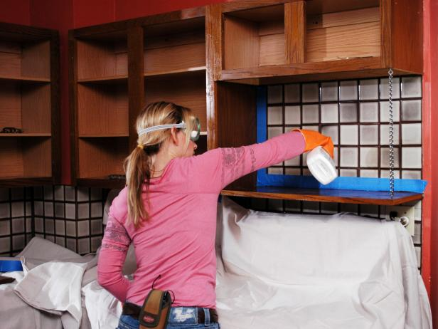 Amy uses a spray bottle of cleaner to wipe off the tiled and cabinets before doing the cabinet upgrade.