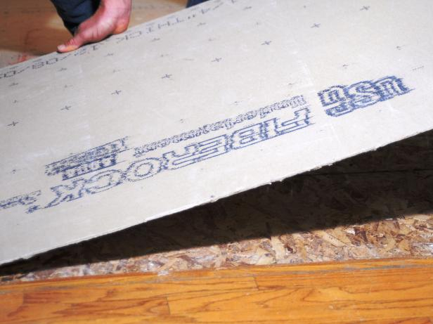Laying cement board on the floor to add tile over it.