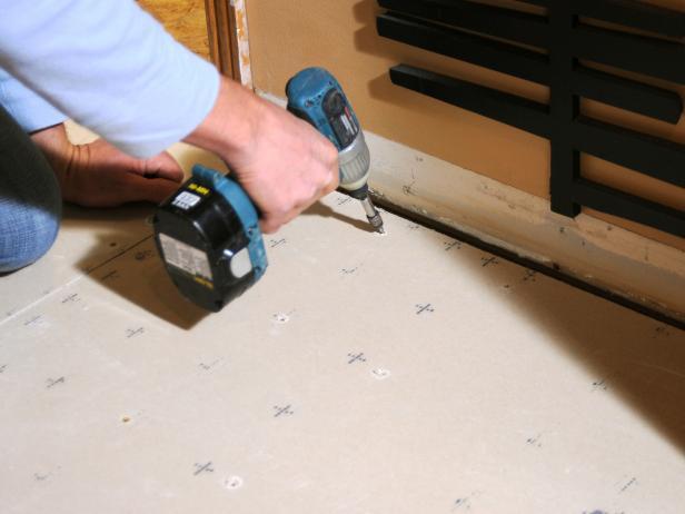 Josh uses a drill to attach the cement board.