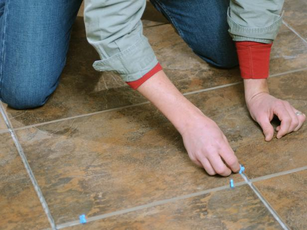 Closeup of man on his knees adding spacers to the tile.