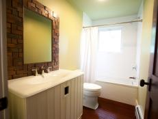 A clean, uncluttered bathroom conjoins two bedrooms in the cabin's unfurnished guest quarters.