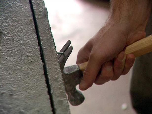 Carefully use a hammer and the new screws to pry each side away from the concrete slab.