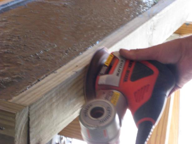 Run an orbital sander (without sandpaper) along the sides of the frame, to vibrate bubbles out of the concrete.