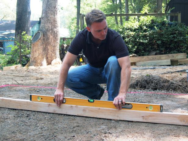 To make sure your area is level, place a long, straight 2X4 on edge across the area, then, place a three foot level on the board and adjust the gravel as necessary.