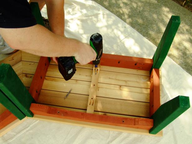 Use a drill to secure the bench slats for the top of the bench.