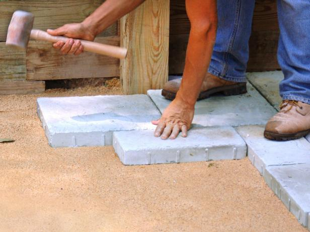 Use a mallet to hammer in the pavers to use as stepping stones. Fill in a small area, and then, check to see that they are even. Remember, you want a slight slope for drainage. Make any necessary adjustments with the rubber mallet.