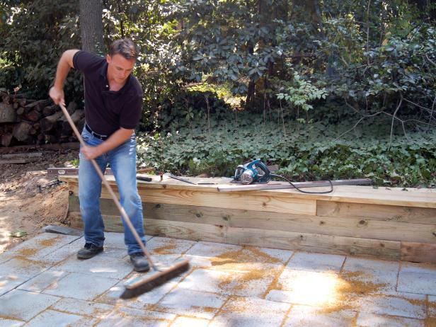 Now that the pavers are set in the base, use a push broom to fill in the joints with a fine layer of sand. Then, sweep off the excess sand from the patio surface.