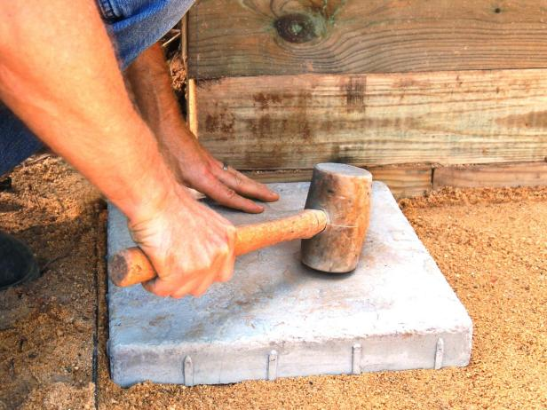 Now that you have a firm, flat base, you're ready to begin installing your pavers. Start in the corner, setting each paver in the sand by tapping it lightly with a rubber mallet.