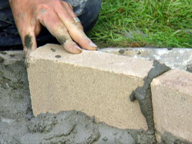 Fill the gaps in between bricks with wet mortar, scraping away any excess. Make sure to measure the inside and outside edges of the wall periodically to maintain the wall's thickness and circular shape.