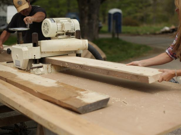 Run planks though the planer, stripping a small amount of wood from each side as you plane. While the board is going through the planer, manually adjust the depth of the cut to compensate for irregular thickness (or twist) over the board's length.