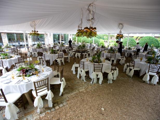 A tent is elegantly decorated with lighting fixtures for a wedding reception at Blackberry Farm.