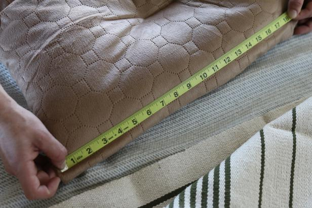Lay the pet bed out on a flat level surface then use the measuring tape to determine its length and width.