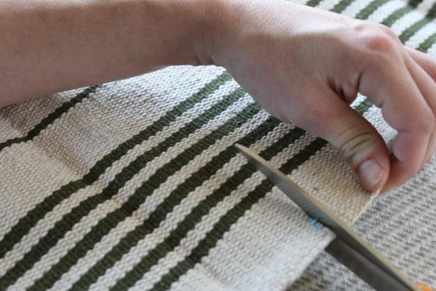 Use dressmaker shears to cut two of the flat weave rugs into top and bottom panels for the slipcover.